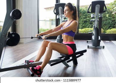 Woman doing exercise for her back in the gym. Seated cable row.
