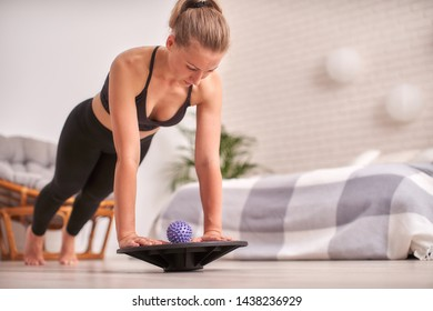 woman doing exercise on a special simulator balancer. blonde athletic sportswear, home did exercise strengthens the muscles. the girl keeps her balance balancing on the sports equipment.copy space.