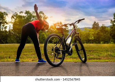 Woman doing exercise,  relaxing after riding bikes  on sunset at park, lifestyle, healthy concept