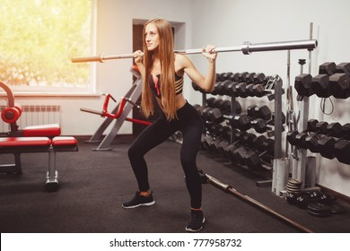 Woman doing an exercise squat with barbell in gym. Concept fitness