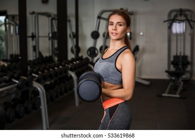 Woman doing exercises with dumbbells in the gym