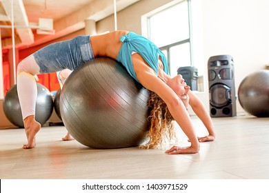 Woman doing exercises with fitball in fitness gym class. Engaging core abdominal muscles. Image concept of healthy lifestyle for women.