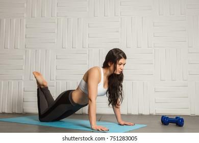Woman is doing exercises indoors full length, grey loft studio background.