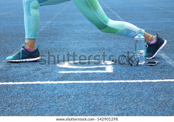 Woman doing exercises on athletic track with mobile phone