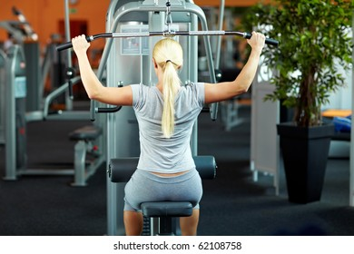 Woman doing exercises on a lat machine in a gym