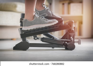 Woman doing exercises on stepper at home