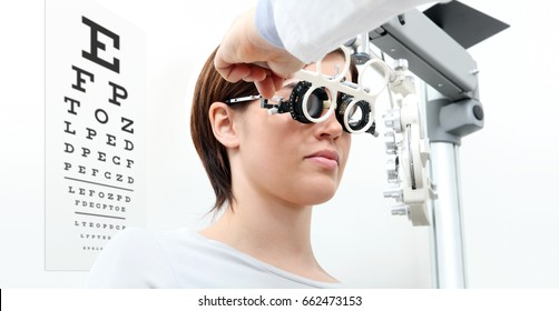 woman doing eyesight measurement with trial frame and visual test chart on white
