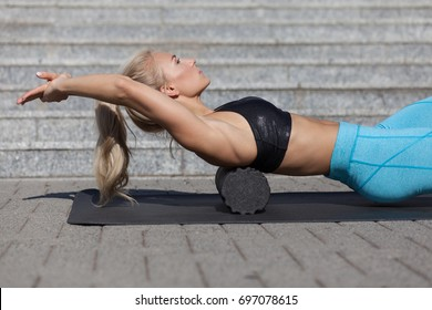 woman doing fascia exercise with foam roller on back