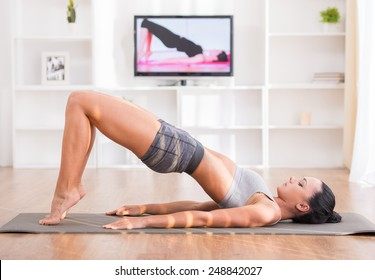 Woman is doing fitness at home on her living room floor while watching and participating in a class.