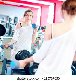 Woman doing fitness training  with dumbbell weights in a gym