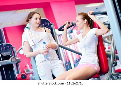 Woman doing fitness training on a butterfly machine with weights in a gym with friend