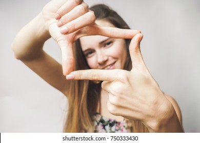 Woman doing frame with hands,smiling, looking at the camera