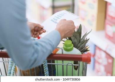 Woman doing grocery shopping at the supermarket, she is pushing a full shopping cart and checking a list