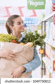 Woman doing grocery shopping at the supermarket, she is holding a grocery bag filled with fresh vegetables
