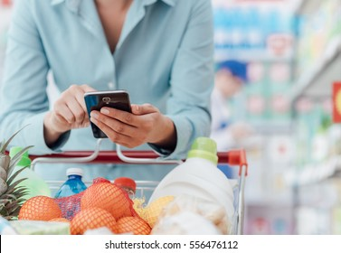 Woman doing grocery shopping at the supermarket, she is leaning on the shopping cart and connecting with her phone, apps and retail concept