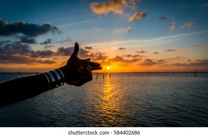 Woman doing gun sign shooting the sun at golden sunset time on the lake, Hello summer concept