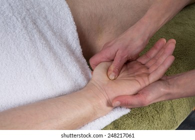 Woman doing a hand massage to a man in the spa salon