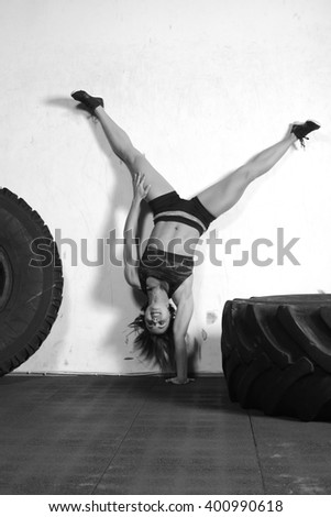 woman doing handstand against concrete wall stock photo
