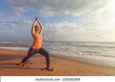 Woman doing Hatha yoga asana Virabhadrasana outdoors on ocean beach on sunset. Kerala, India