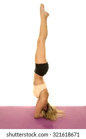 a woman doing a head stand, showing off her balance on her fitness mat.