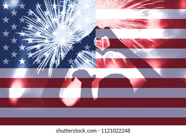 Woman doing heart shape with her hands at 4th of July, American Independence day celebrations. Fireworks and the flag of United States blending