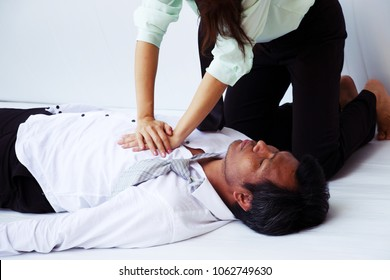 Woman is doing helping first aid as CPR for businessman