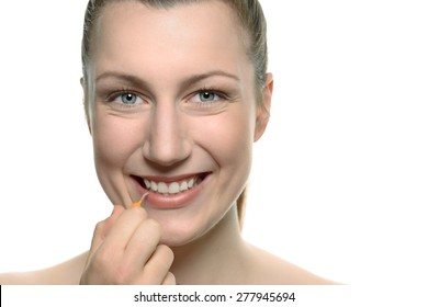 Woman doing her daily routine of brushing and cleaning between her teeth with an interdental brush in a dental care and oral hygiene concept, close up to her mouth
