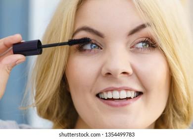 Woman doing her make up using black mascara brushing eyelashes. Female beauty visage concept.