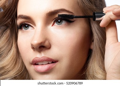 woman doing her makeup eyelashes black mascara