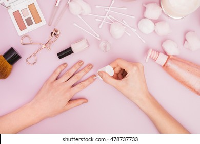 Woman Doing Her Nails on a Pink Pastel Background
