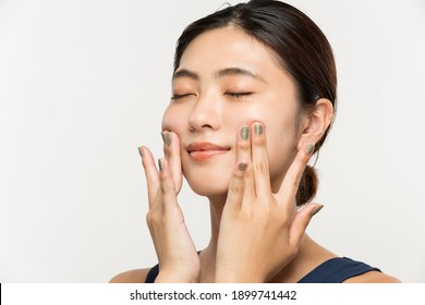 The woman is doing her own facial massage.