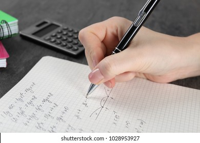Woman doing homework in exercise book, closeup