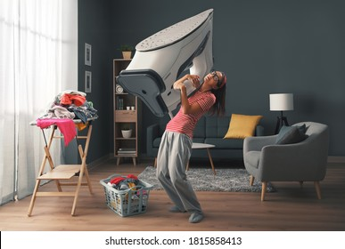 Woman doing household chores and holding a huge heavy iron, stress and housework concept
