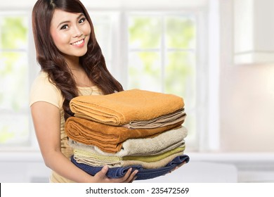 woman doing a housework holding laundry at home