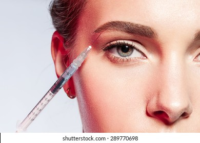 ?lose-up of a woman doing an injection under the eyebrow