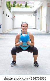 Woman doing the kettlebell squat for muscle strengthening exercise, outdoors