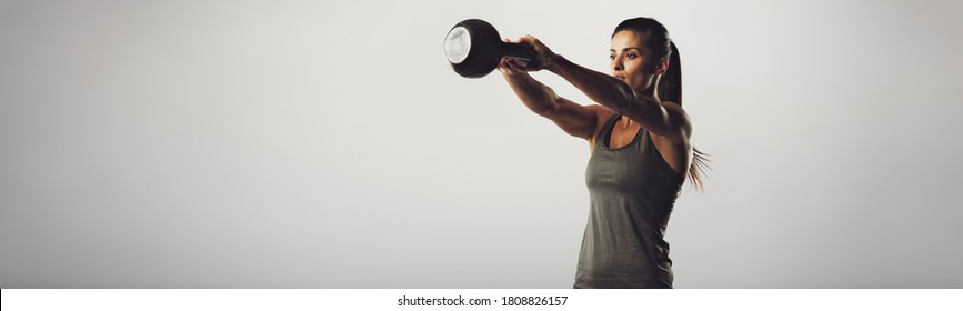 Woman doing kettlebell swings in gym outfit shot on in isolated grey background. Fit woman doing healthy workout.