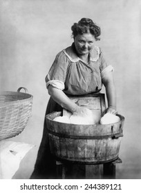 Woman doing laundry in wooden tub and metal washboard, ca. 1905.