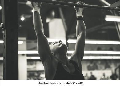 woman doing lifting up on the gym bar