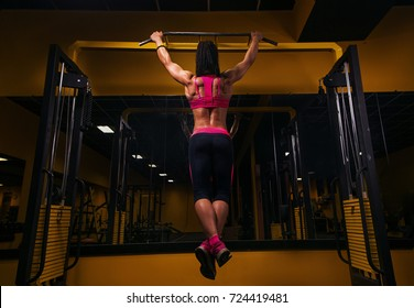 woman doing lifting up on the gym bar