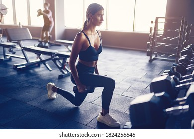 Woman doing lunges exercise with dumbbells in gym.