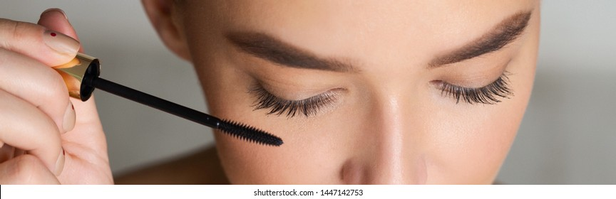 Woman Doing Makeup, Applying Black Mascara on her Eyelashes, Closeup, Panorama
