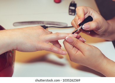Woman doing manicure in beauty salon. Close-up, selective focus.