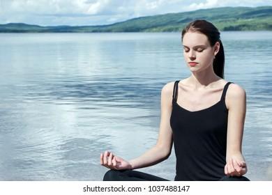 woman doing meditation by lake