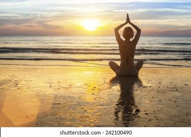 Woman doing meditation near the ocean. Yoga silhouette.