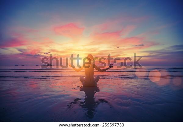 Woman doing meditation near the ocean beach. Yoga silhouette.