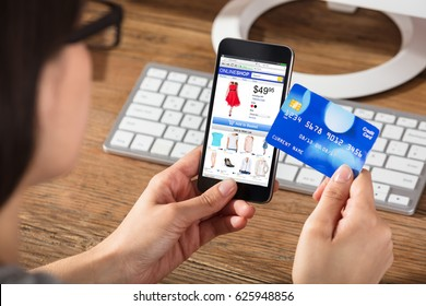 Woman Doing Online Shopping Using Cell Phone And Credit Card