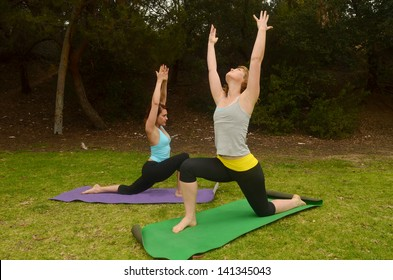 Woman doing outdoor yoga/Outdoor Yoga.Two woman are engaged in yoga in outdoor setting