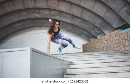 Woman doing parkour in the city on a sunny day.