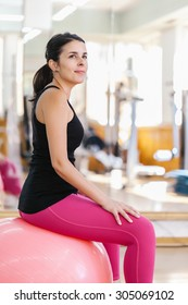 Woman Doing Pilates Exercises with a Ball